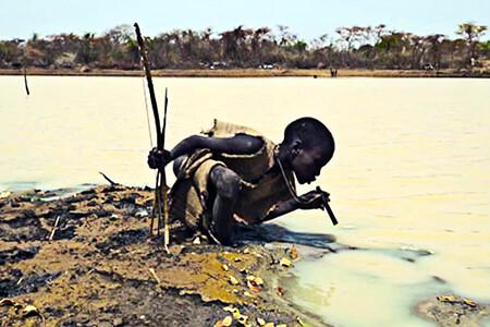 Foto de un niño en África bebiendo agua contaminada